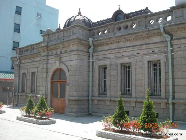 Exterior view of the former Japanese bank, a light stone building with pale green guttering, a brown door and decorative trees in front of it.