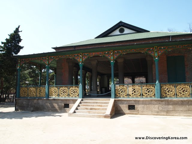 Jeonghwangeon, a pavilion with delicate gold and green railings outside, green pillars and stone steps leading up. Red and green fretwork in the eaves, and blue sky behind.