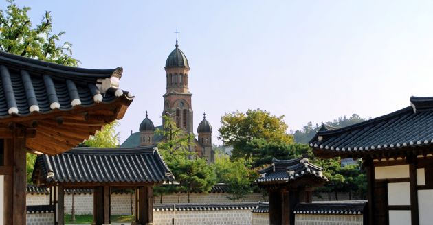View towards the cathedral at Jeonju, in the background the cathedral has three dome shaped spires and arched windows. In the foreground are the traditional dark tile curved roofs of the hanok houses.