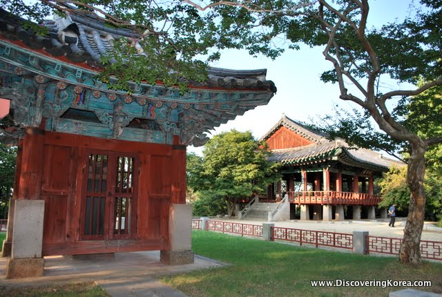 On the left is a hanok, a traditional house in Jeonju, with red wooden doors, and ornate carved roof, in turquoise, to the right is a wooden house with stone steps up to the door, in between is grass and trees on a sunny day.