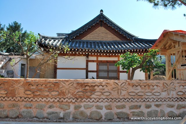A traditional hanok house, with dark tiled, curved roof, in front is a stone wall with carving in the stone, on a bright sunny day.