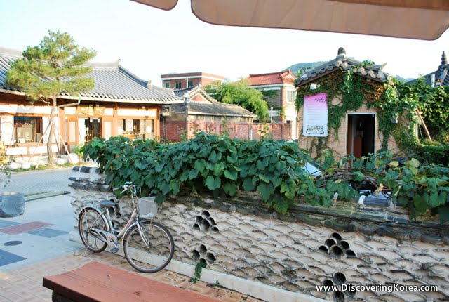 A neighborhood street in Jeonju, with a stone wall and a bicycle leaning up against it, with homes in the background with the traditional curved tile roof.