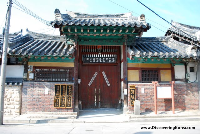Imposing entrance to the Hakindang in Jeonju, a large wooden door, with a curved roof, and brick walls either side.