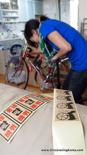 A woman using a hand pump to inflate a bicycle tire in the background. In the foreground are rows of printed stickers in black and red.