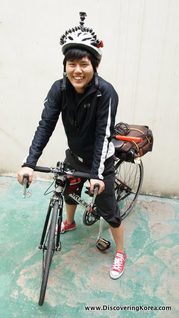 A woman pictured smiling at the camera on a bicycle, wearing a black outfit with a white helmet, on a pale green concrete surface.