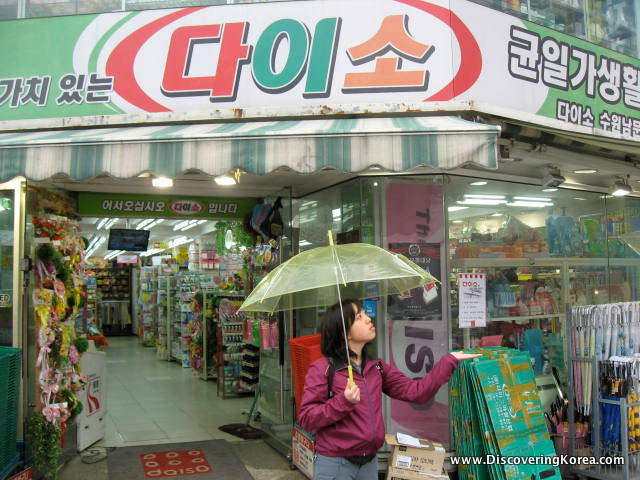 A woman carrying a green umbrella walks out of a shop, in the background the inside of the shop is visible, and to the top of the frame Korean lettering.