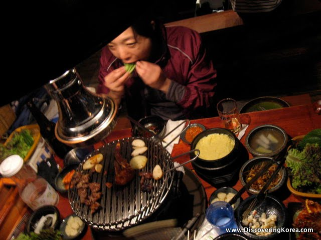 A woman sitting at a table filled with food in various bowls, eating. In the center of the frame is a tabletop grill containing meat.