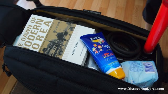 A black cycling saddle bag, packed with a book, sunscreen and and other items below. On a wooden floor.