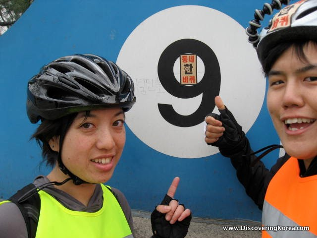 Two women pictured wearing bicycle helmets and reflective safety vests pointing at a number 9 on a blue and white wall.