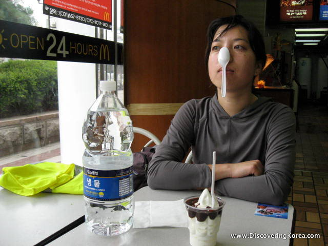A woman in a cafe, with a plastic water bottle on the table in front of her, and an ice cream sundae.