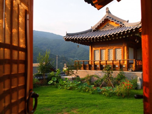An ornate Korean house in the sunshine with mountain backdrop, green lawn to the front.
