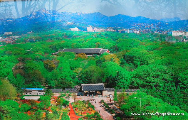 Jongmyo Ancestral Shrine seen from above, nestled in green trees, with a soft focus backdrop of mountains and cityscape.