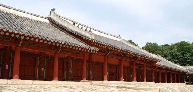 Exterior view of a very long building at Jongmyo Royal Shrine. The low red building has pillars, and a dark roof.