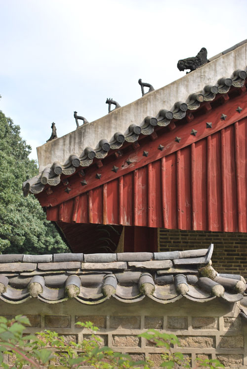 Close up detail of the roof of Jongmyo royal shrine, with red overhang.