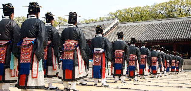Men in a line, dressed in black and multicolored robes, take part in the Jongmyo Great Rite, outside the royal shrine.