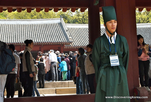 A man, to the right of the frame, dressed in dark green stands in front of a pillar at Jongmyo royal shrine. Pedestrian crowds in the background.
