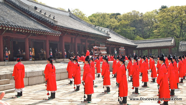 Group of people dressed in red tunics, performing a ritual outside the Jongmyo shrine. The dark red building to the left of the frame.