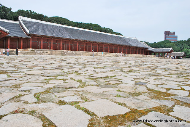 View of the long red pillared building of Jongmyo Royal Shrine. In the foreground is the stone terrace leading to the shrine.