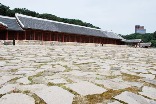 Paved area outside the Jongmyo Royal Shrine, with the building in the background, red pillars and dark roof.