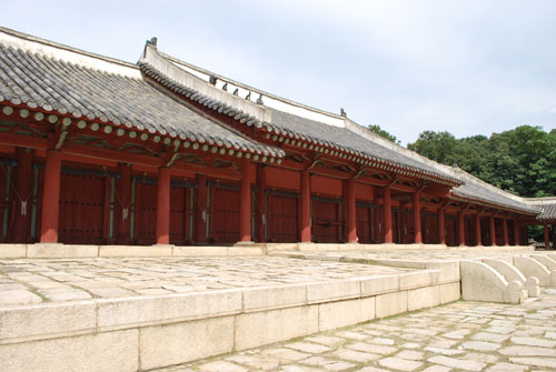 Jongmyo Royal Shrine, a low red building, with dark tiled roof, on light stone.