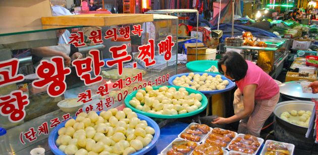 A food vendor's stall at Jungang Traditional Market in Seoul, various vegetables and meat produce in plastic bowls, with a glass cabinet and red Korean writing. A woman in the foreground inspects the wares.