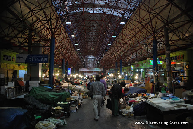 Jungang Traditional market at night, a high ceilinged warehouse with stall vendors on either side of a pedestrian walkway.