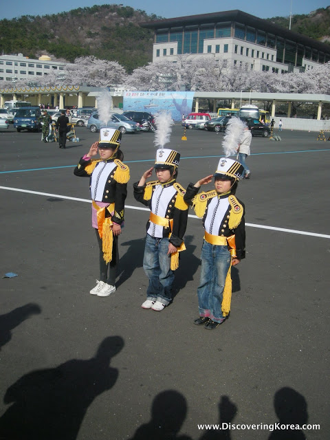 Three Korean middle school students in marching band uniforms are saluting.