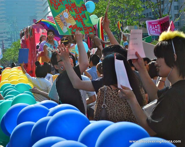A crowd of people all holding up banners and placards, to the left of the frame is a long line of blue, green and yellow balloons on a bright sunny day.