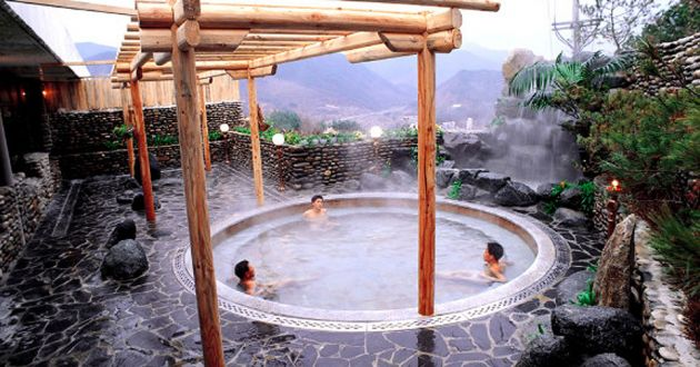 An outdoor hot spa pool, under a wooden pergola, set into tiled patio with soft focus mountains in the background.