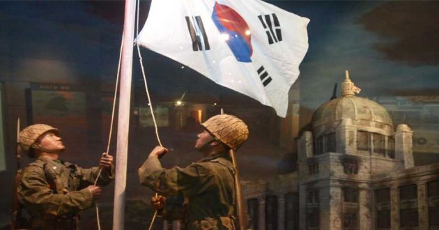 Two soldiers raise a white, blue, red and black flag with a soft focus dark background and a building to the right of the frame.