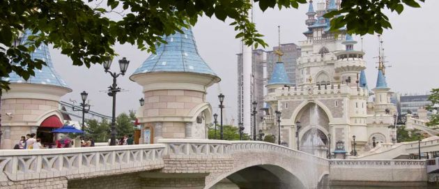 View across a bridge to the impressive stone building of Lotte World Amusement Park. Circular turrets with light blue roofs and an arched entranceway, it looks like a castle.