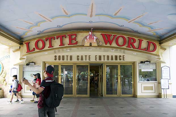 Entrance to Lotte World, glass doors surrounded by a light yellow wall with red lettering, in front of the entrance various people walking and standing around.