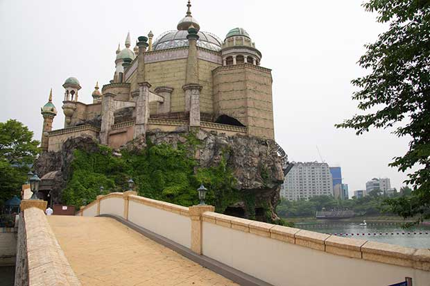 View over a bridge, with the river to the right of the frame, an impressive stone building with dome roof and pillars, built on a cliff face. In the background is Seoul city.