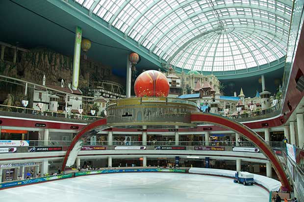 A glass dome ceiling above a shopping arcade, with a large structure in the center, with an arched frame above it.