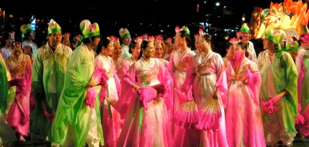 Ladies dressed in long pink robes, and men in long green robes, with elaborate hats, carrying fans gather at the Seoul Lotus Lantern Festival.