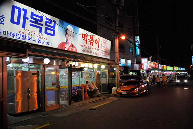Night time view of Ma Bok-lim restaurant, a glass shop front with a brightly lit sign above it.