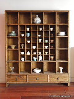 Ceramic rice beer cups and ceramic vases in a wooden display cabinet, with drawers at the bottom, standing on a wooden floor.