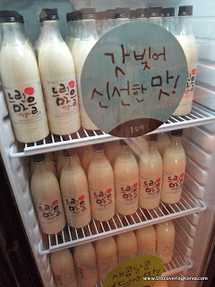 A display refrigerator containing bottles of Makgeolli rice beer. A sign with Korean lettering on the front of the fridge.