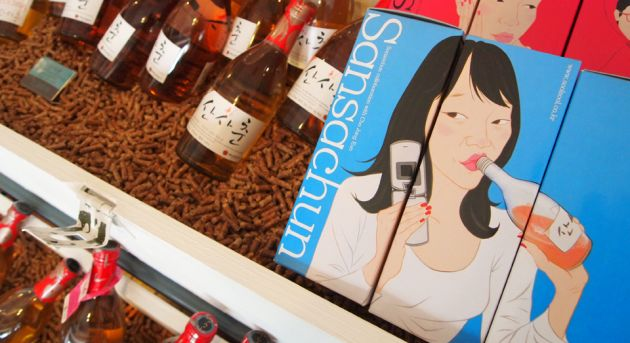 Bottles of rice beer to the left of the frame, with a picture of a woman drinking from a bottle, holding an old fashioned cell phone on a blue background.