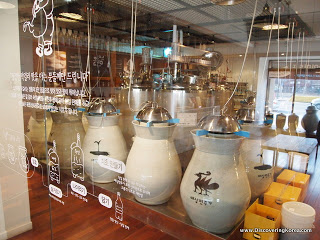Rice beer being brewed in light stone colored ceramic pots, with metal tops behind a glass shop front.
