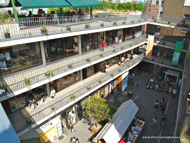 Looking down at a shopping mall, open balconies on three different levels, with shops and cafes, and the road below.