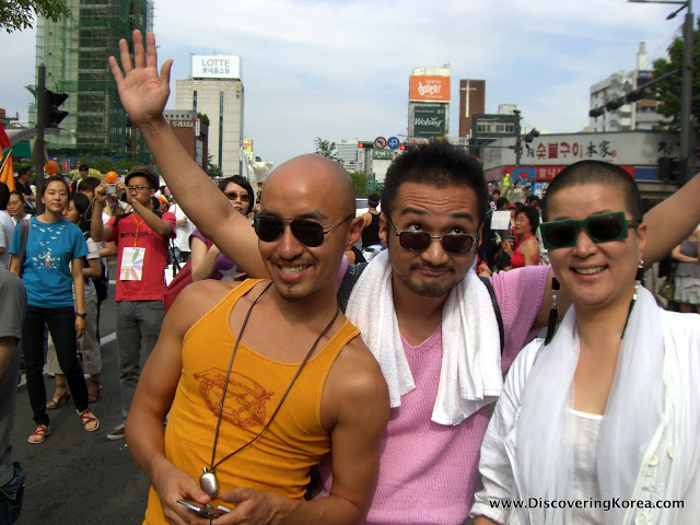 Two men and a woman at a parade, one man with his arms in the air celebrating, with shops and city scene behind.