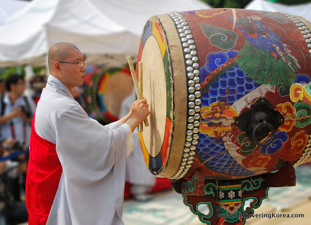 A Buddhist monk dressed in white robe, with a red cape, at Bongwonsa temple, playing a large, multicolored drum to the right of the frame.
