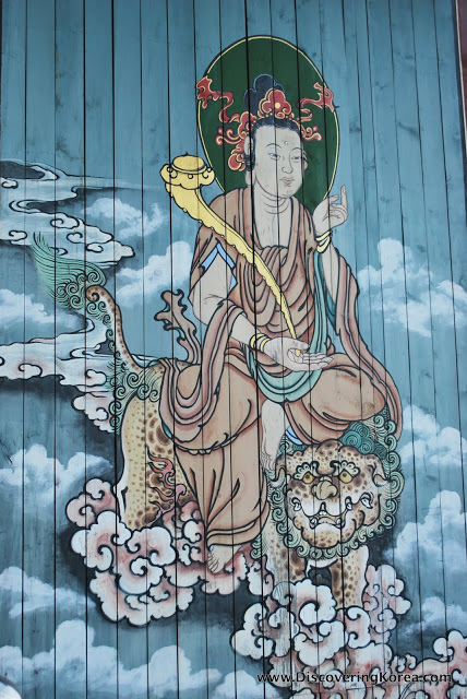 Mural of a traditional Korean man seated on a tiger, with a large pipe in his hand. The background is blue sky with clouds.
