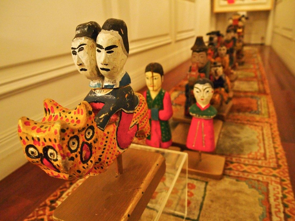 Wooden carvings, in a long line, depicting people riding on mythical animals, people walking, dressed in traditional Korean clothes, on a patterned carpet.