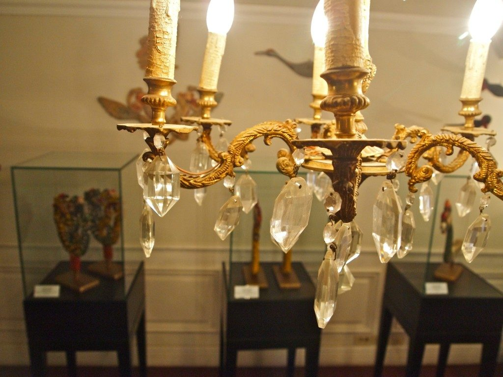Close up of a chandelier, gold colored with crystals hanging down. In the background are glass display cases at the Musee Shuim.
