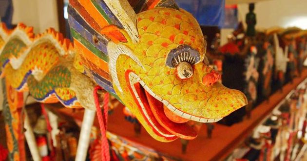 Close up of a carved wooden dragon, with yellow and red scales, multicolored body and wings at Musee Shuim.