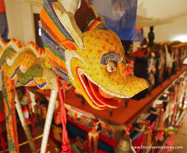 Art from the Musee Shin depicting a multicolored wooden dragon sculputure with soft focus background.