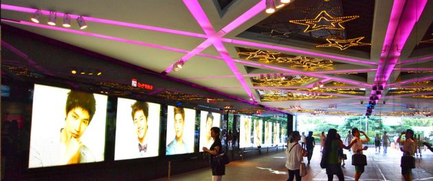 A shopping arcade in Myeongdong district, with pink neon lights, and neon stars on the ceiling. Images of young people on brightly lit screens, and pedestrians.
