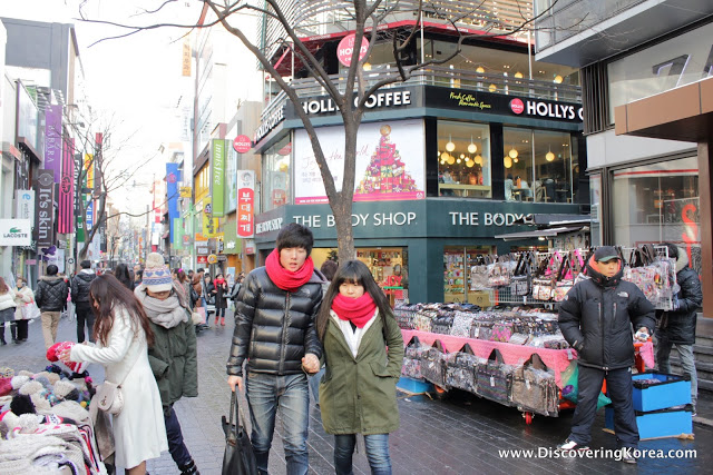 A pedestrian street in Myeongdong shopping district. In the center of the frame, two people dressed for winter, with red scarfs, to each side are shop fronts, market stalls and pedestrians looking at the wares.